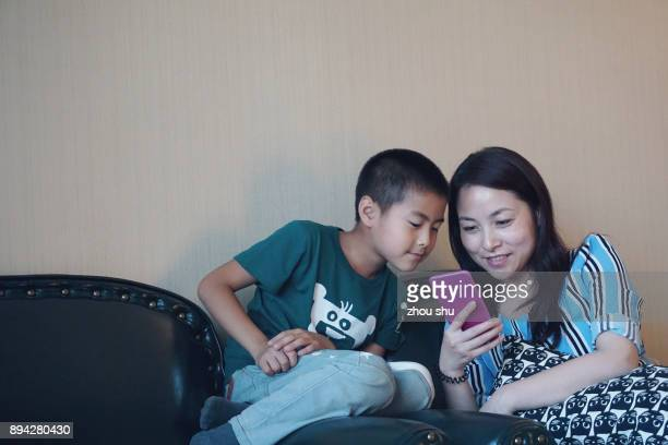 Mon and son happily looking at the phone screen