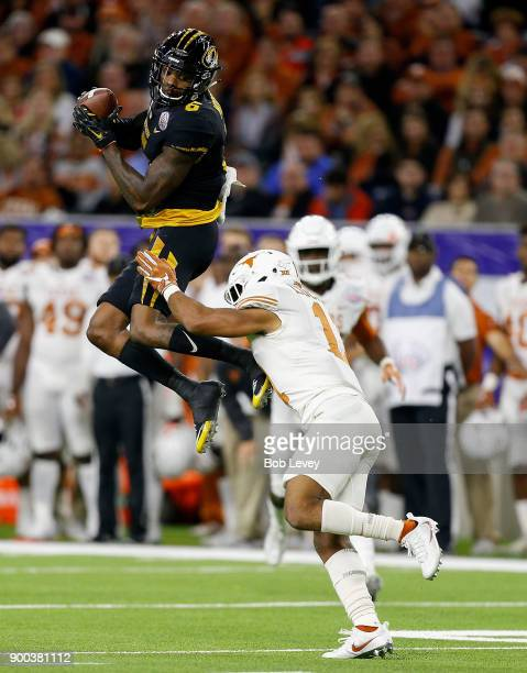 Mon Moore of the Missouri Tigers catches a pass in front of PJ Locke III of the Texas Longhorns during the Academy Sports Outdoors Bowl at NRG...