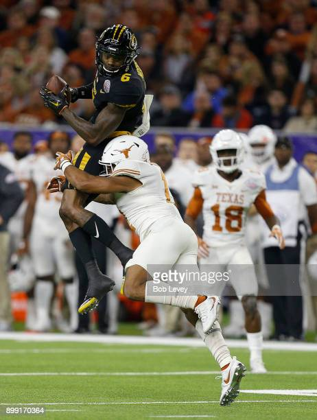 Mon Moore of the Missouri Tigers makes a catch as he is hit by PJ Locke III of the Texas Longhorns during the Academy Sports Outdoors Bowl at NRG...