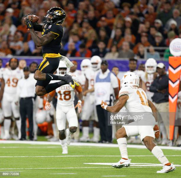 Mon Moore of the Missouri Tigers makes a catch in front of PJ Locke III of the Texas Longhorns during the Academy Sports Outdoors Bowl at NRG Stadium...