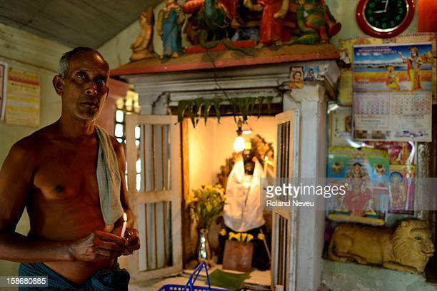A mon of Indian descent in Mawlamyine is attending a shrine at an old Hindu temple