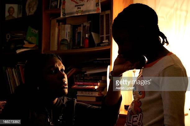 ALLEYNE Mona Alleyne checks the cheek of her sevenyearold granddaughter Daja'el in their Scarborough apartment Tuesday afternoon December 11 2007...