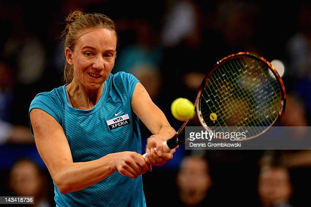 Mona Barthel of Germany plays a backhand in her match against Marion Bartoli of France during day four of the WTA Porsche Tennis Grand Prix at...