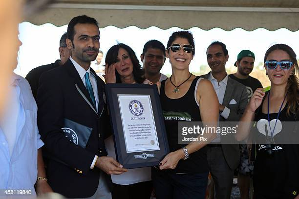 Mona Naffaa receives the Guinness certificate from a Guinness official for breaking the record of the largest floating image that she organized with...
