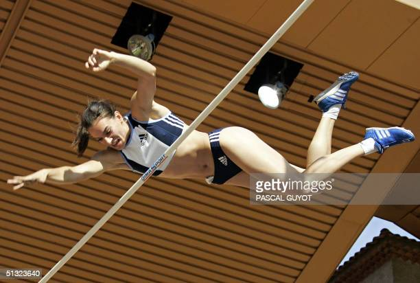 """Russian Yelena Isinbayeva competes during the pole vault competition of the IAAF """"World Athletics Finals"""", 19 September 2004 at the Louis II stadium..."""