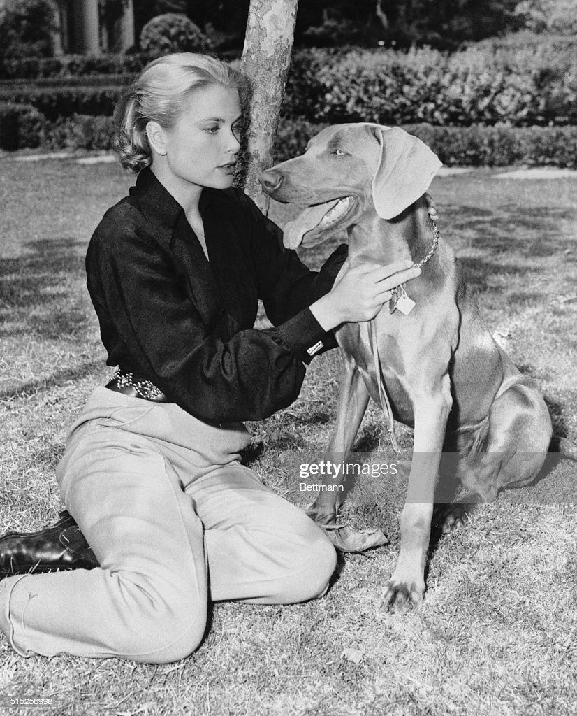 Grace Kelly Petting a Dog : News Photo