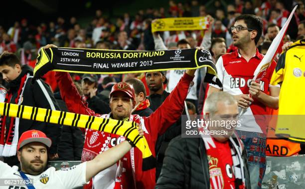 Monaco supporters with Borussia scarves react in the stadium after the match was postponed amid an explosion near the bus of Borussia Dortmund some...
