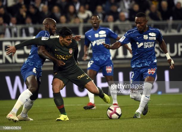 Monaco's Colombian forward Falcao vies with Amiens' French defender Prince Desir Gouano and Amiens' Beninese defender Khaled Adenon during the French...