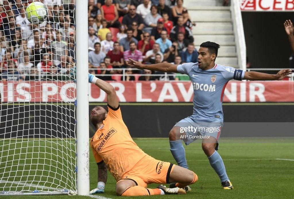 TOPSHOT - Monaco's Colombian forward Radamel Falcao (R) shoots and scores against Dijon's French goalkeeper Baptiste Reynet (L) during the French Ligue 1 football match between Dijon FCO and AS Monaco, on August 13, 2017 at Gaston Gerard stadium in Dijon, northern France. /