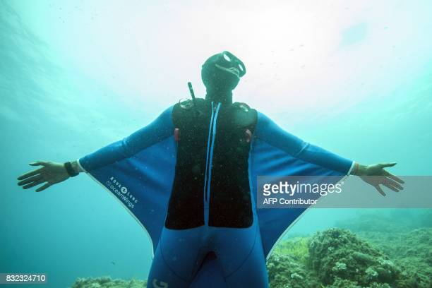 Monaco's freediver Pierre Frolla wearing a prototype of an ''Oceanwings' wetsuit glides through the water on August 13, 2017 in the Mediterranean sea...