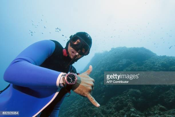 Monaco's freediver Pierre Frolla wearing a prototype of an ''Oceanwings' wetsuit gestures as he glides through the water on August 13, 2017 in the...