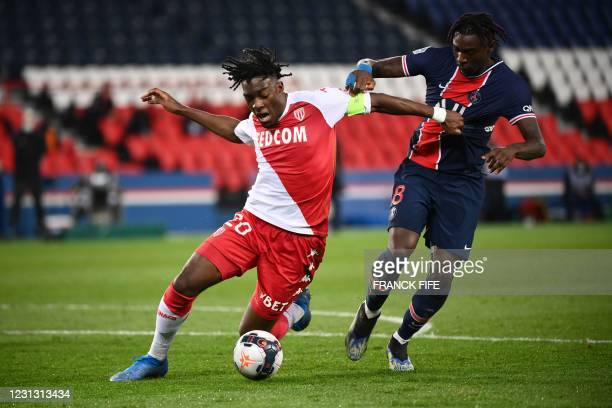 Monaco's French defender Axel Disasi fights for the ball with Paris Saint-Germain's Italian forward Moise Kean during the French L1 football match...