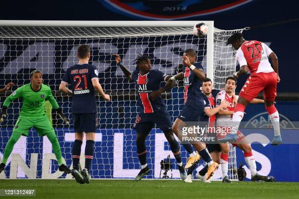 Monaco's French defender Axel Disasi heads the ball past Paris Saint-Germain's Italian forward Moise Kean and Paris Saint-Germain's French defender...