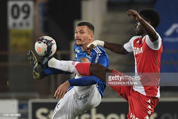Monacos French defender Benoit Badiashile Mukinayi fights for the ball with Strasbourgs French forward Ludovic Ajorque during the French L1 football...