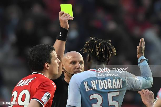 Monaco's French defender Kevin N'Doram receives a yellow card by French referee Amaury Delerue during the French L1 football match Rennes vs Monaco...