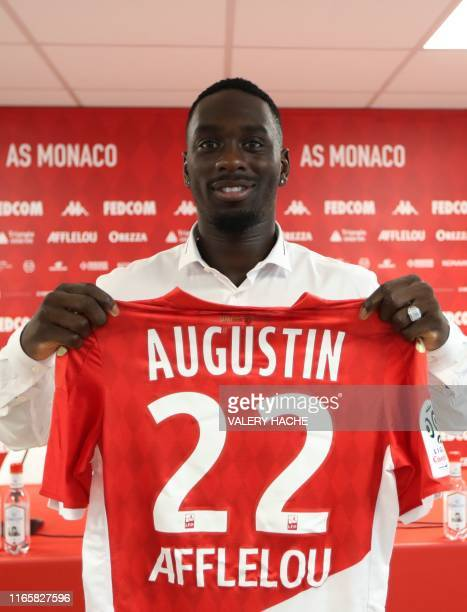 Monaco's French forward JeanKevin Augustin poses with his jersey after a press conference held for his presentation in La Turbie near Monaco on...