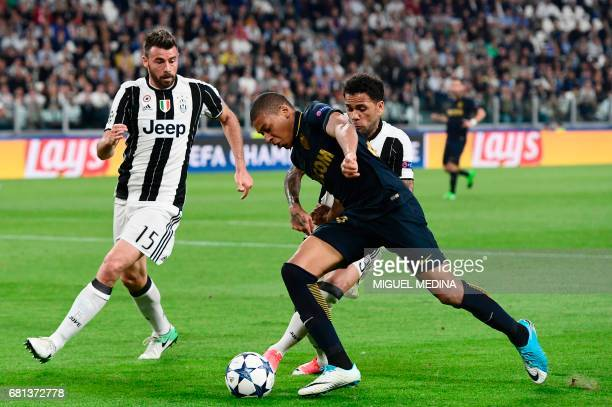 Monaco's French forward Kylian Mbappe fights for the ball with Juventus Defender from Brazil Dani Alves and Juventus' defender from Italy Andrea...