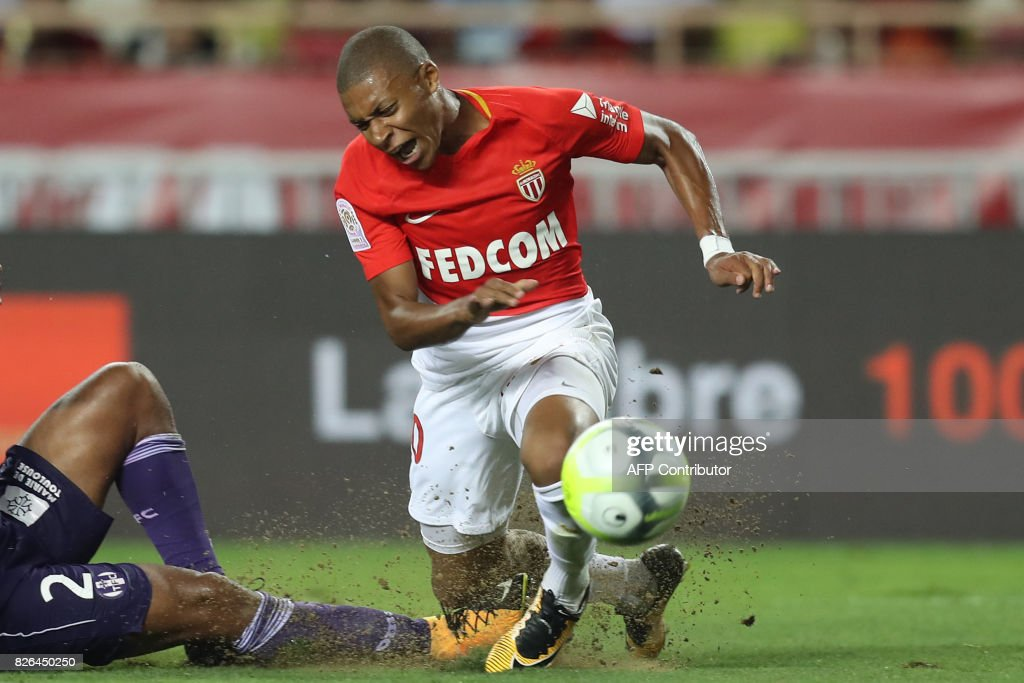 TOPSHOT - Monaco's French forward Kylian Mbappe reacts as he falls during the French L1 football match between Monaco (ASM) and Toulouse (TFC) at Louis II Stadium in Monaco on August 4, 2017. /