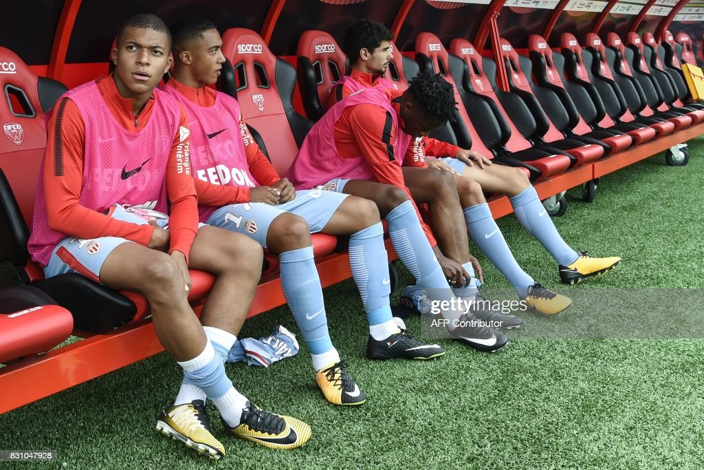 Monaco's French forward Kylian Mbappe (L) sits on the bench during the French Ligue 1 football match between Dijon FCO and AS Monaco, on August 13, 2017 at Gaston Gerard stadium in Dijon, northern France. /