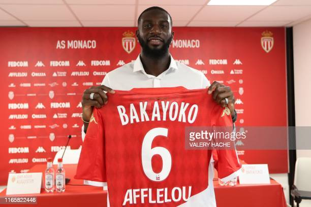 Monaco's French midfielder Tiemoue Bakayoko poses with his jersey after a press conference held for his presentation in La Turbie near Monaco on...