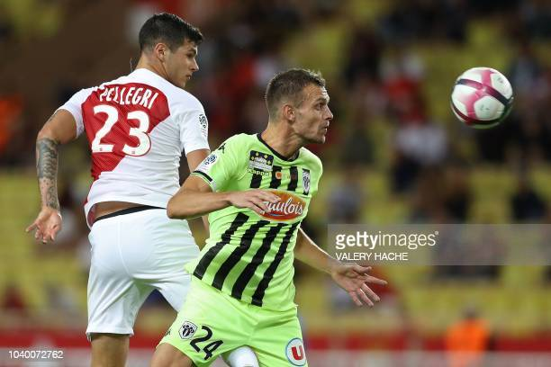 Monaco's Italian forward Pietro Pellegri heads the ball with Angers' French defender Romain Thomas during the French L1 football match Monaco vs...