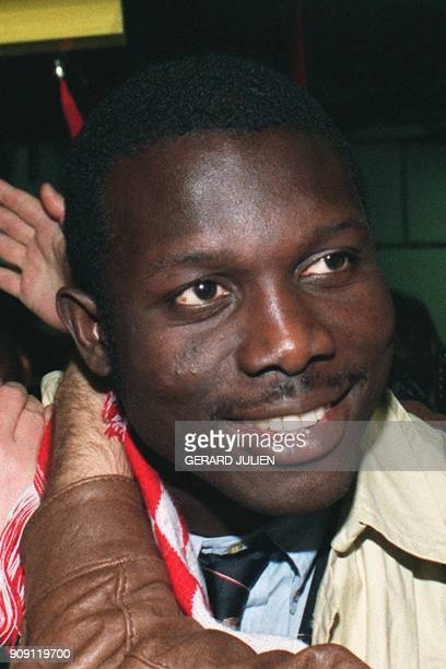 Monaco's Liberian forward George Weah smiles as he is congratulated by fans upon the team's arrival 16 April 1992 at the airport in Nice following...