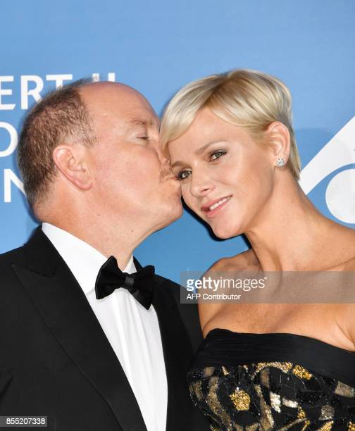 Monaco's Prince Albert embraces Princess Charlene during the MonteCarlo Gala for the Global Ocean in Monaco on September 28 2017 / AFP PHOTO / YANN...