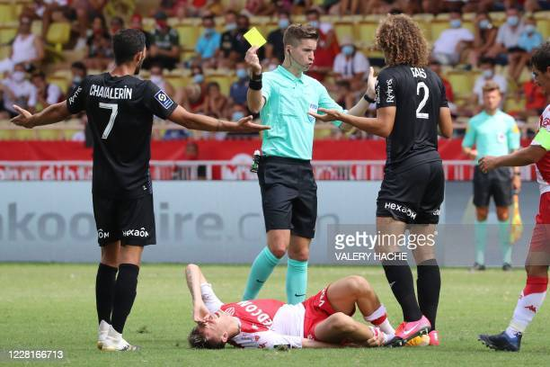 Monaco's Russian midfielder Aleksandr Golovin lies on the ground as Reims' Belgian defender Wout Faes receives a yellow card by French referee...