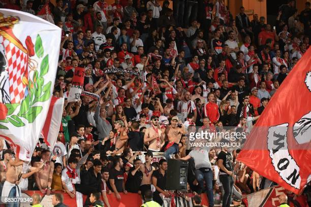 Monaco's supporters celebrate their team's victory at the end of the French L1 football match between Monaco and Lille at the Louis II Stadium in...