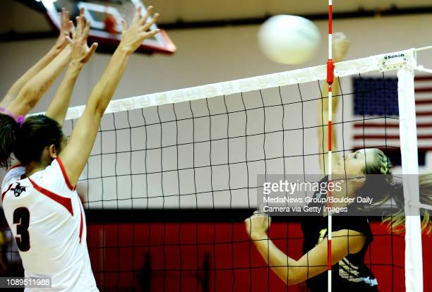 Monarch senior Allyson Porter spikes the ball over the fingertips of Fairview senior Allie Johnson during play at Fairview High School in Boulder on...