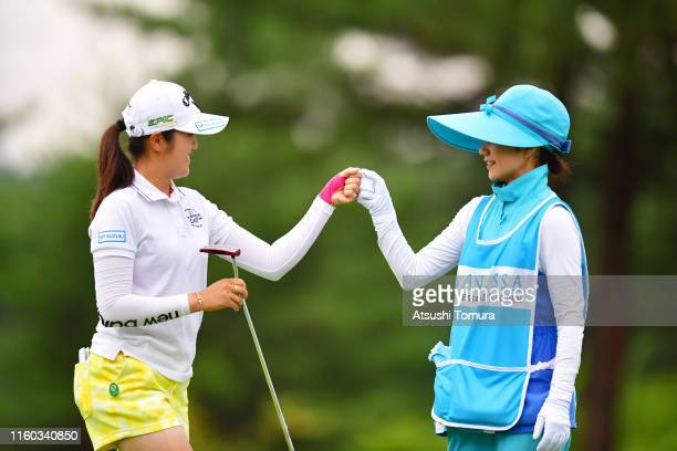 Mone Inami of Japan fist bumps with her caddie after holing out on the 18th green during the third round of the Shiseido Anessa Ladies Open at...