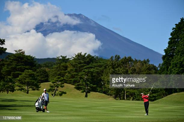 Mone Inami of Japan hits her second shot on the 14th hole while Mt Fuji is seen on the background during the final round of the Stanley Ladies Golf...