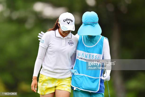 Mone Inami of Japan is congratulated by her caddie after holing out on the 18th green during the third round of the Shiseido Anessa Ladies Open at...