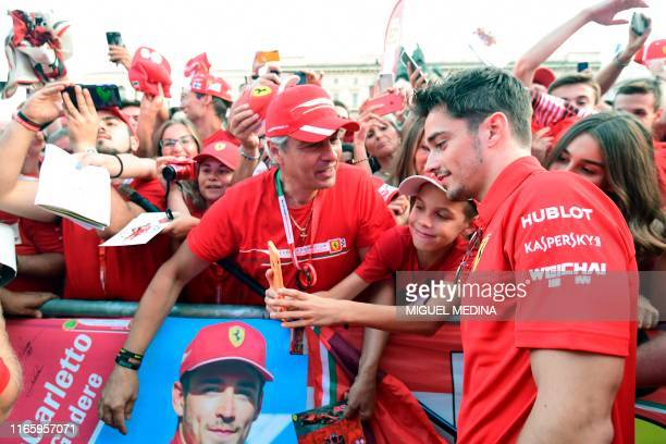 Monegasque Ferrari's pilot Charles Leclerc pose with the public for a selfie as he arrive in Piazza Duomo in Milan on Septembre 4 2019 for the...