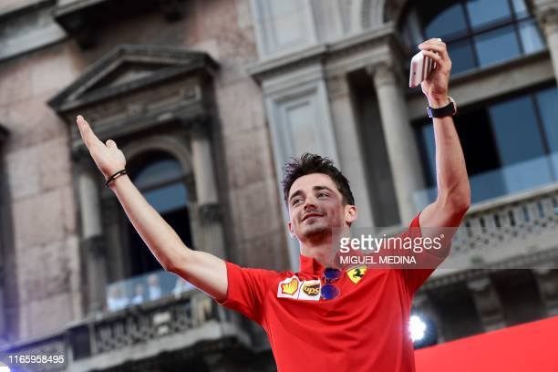 Monegasque Ferrari's pilot Charles Leclerc salutes F1 fans as he arrives in Piazza Duomo in Milan on Septembre 4 2019 for the presentation of cars...
