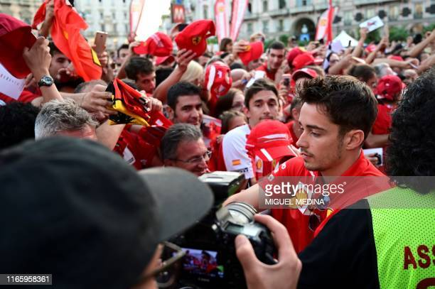 Monegasque Ferrari's pilot Charles Leclerc signs autographes as he arrives in Piazza Duomo in Milan on Septembre 4 2019 for the presentation of cars...