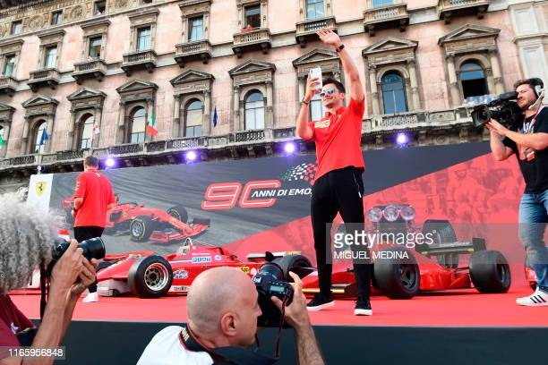 Monegasque Ferrari's pilot Charles Leclerc takes a picture with his phone as he arrives at Piazza Duomo in Milan on September 4, 2019 during the...