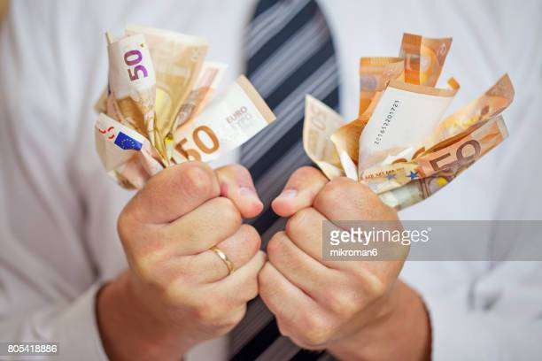 Money addicted, Greedy businessman squeezing money. Love of money.