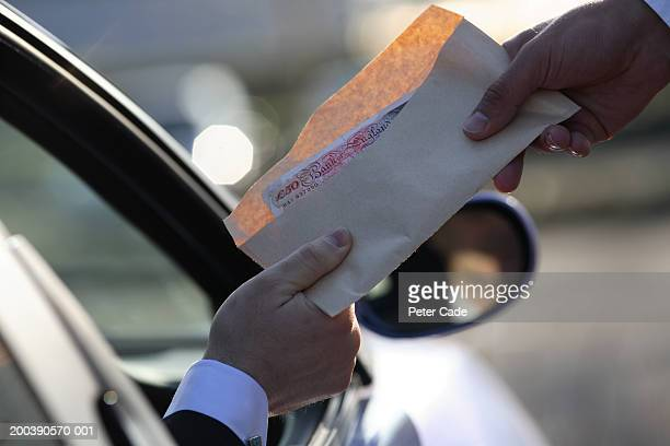 money being handed over from car, close-up - corruption stock pictures, royalty-free photos & images