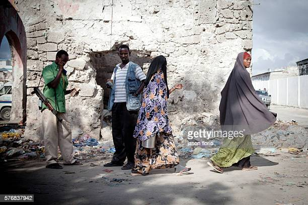 A money changer and local militia man carrying and AK47 gun converse while women in veils walk by in central Mogadishu