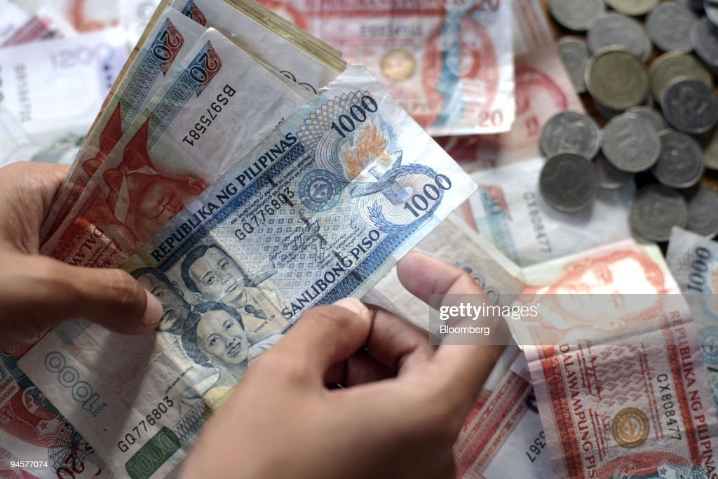 A Money Changer Arranges Pile Of Philippine Peso Notes And News Photo