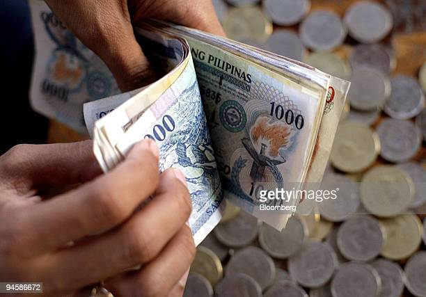 A money changer flips through a pile of Philippine peso notes in Legazpi City the Philippines on Sunday May 20 2007 The Philippine peso appreciated...