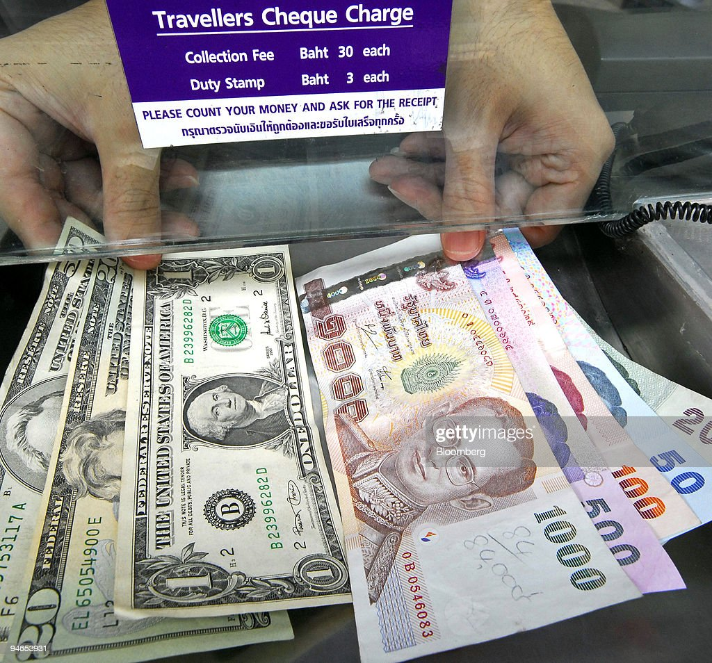 A Money Changer Shows Thai Baht And U S Dollar Banknotes At News Photo