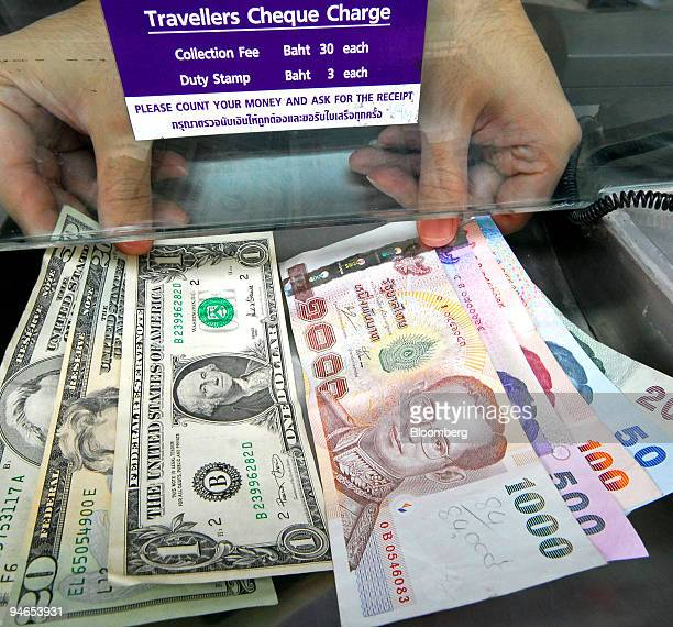 A Money Changer Shows Thai Baht And Us Dollar Banknotes At His Currency Exchange Booth In