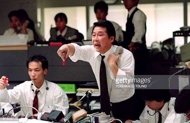 A money dealer calls buying orders 20 January 1992 during a morning session at the Tokyo Stock Exchange AFP PHOTO YOSHIKAZU TSUNO