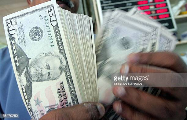 A money dealer counts US dollar notes at a money changer in the Raffles Place financial district of Singapore 20 December 2005 The USD steadied...