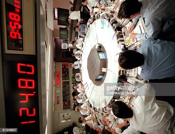 Money dealers are busy trading under the price board quoting 12480 yen against US dollar during the morning session of the Tokyo Foreign Exchange...