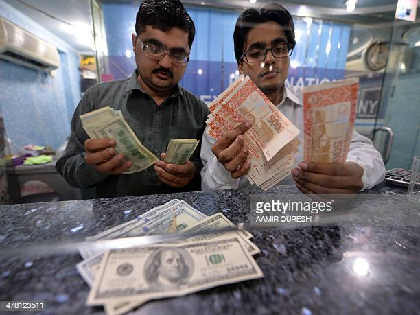 Money dealers counts Pakistani rupees and US dollars at a currency exchange in Islamabad on March 12 2014 Pakistan's finance minister Ishaq Dar on...
