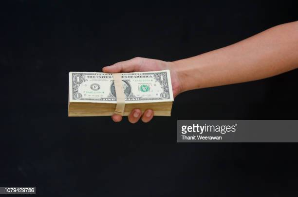 Money dollar in hand hold out with black background, Business and money