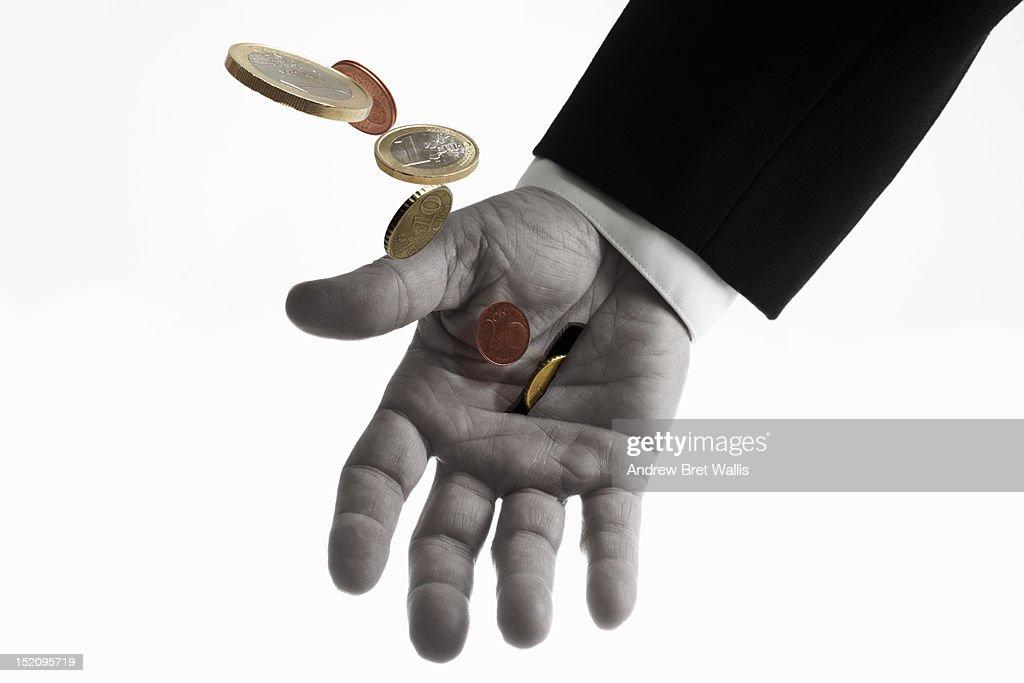 money falling through the slot in a man's hand : Foto de stock